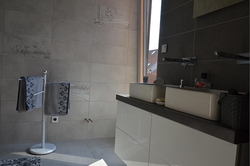 V jedné ze tří koupelen vynikají obklady a dlažby v šedohnědé kombinaci, opět s cementovým vzhledem.