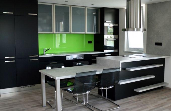 Barevná skleněná deska v kuchyni dokáže rozjasnit celou místnost. V tomto případě byla zvolena sytě zelená v kombinaci s černobílými skříňkami. FOTO: Stylishrooms